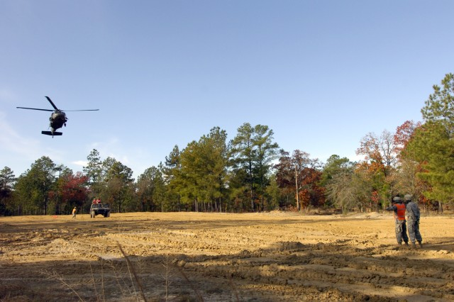 Two Paratroopers from the 407th Brigade Support Battalion, 2nd Brigade Combat Team, 82nd Airborne Division, direct a UH 60 Blackhawk helicopter over a humvee where three Paratroopers are waiting to a attach a humvee to the bottom of Blackhawk during sling load training. The sling load training was part of the 407th BSB Field Training Exercise.  (U.S. Army photo by Sgt. Susan Wilt, 2nd BCT, 82nd Abn. Div. PAO)