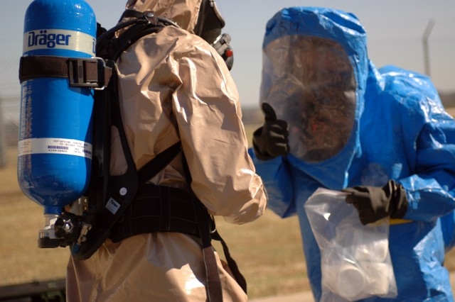 A member of a chemical reconnaissance team gives thumbs up to signal completion of this chemical situational training exercise.