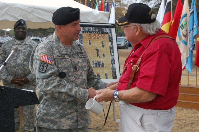 U.S. Army South Command Sgt. Maj. Armando Ramirez presents retired Army Col. Eugene Thompson with an Army South coin and coffee cup. Army South hosted a National Native American Indian Heritage Month celebration in front of the headquarters Nov. 14.