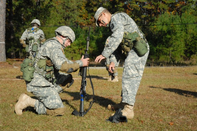 Lopez shows a Soldier in his company how to reattach the hand guard of his M-16 rifle during bayonet assault training.