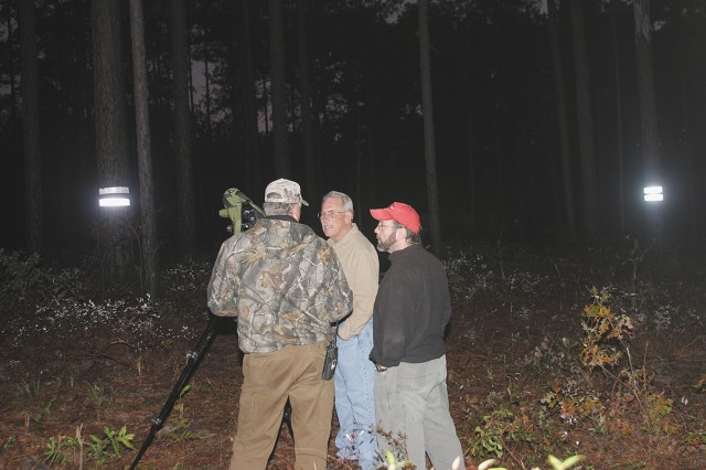 FORT GORDON, Ga.--Woodpeckers released -1  - (Left to right) In the pre-dawn darkness,  Steve Camp, Fort Gordon Fish and Wildlife biologist, Steve Willard, Directorate of Public Works Environmental Division chief, and Robert Drumm, Natural Resources Branch chief stand in a cluster of trees prepared to house a new family of endangered Red-cockaded woodpeckers, Nov. 7, 2008 on Fort Gordon. The nesting trees are marked with light reflecting double bands. Photo by Larry Edmond