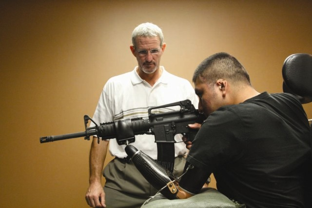 Spc. Marco Robledo aims an M-4 in the Fire Arms Training Simulator at the Walter Reed Army Medical CenterAca,!a,,cs Military Advanced Training Center.