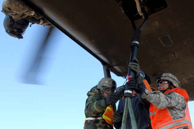 "Spc. Maria Vidales, a 615th Aviation Support Battalion Blackhawk mechanic and Spc. Miguel Balladares, 227th Aviation Battalion hook a HMMWV to a Blackhawk with the help of an instructor while a Blackhawk crewmember watches from above during a Sling Load Certification course conducted by 15th Sustainment Brigade here, Nov. 21.  ""It's a quick rush, everything went by pretty fast,"" Balladares said."
