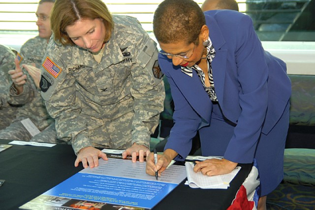 Col. Laura J. Richardson, Fort Myer Military Community-Fort McNair garrison commander, assists Congresswoman Eleanor Holmes Norton in signing the Army Community Covenant.