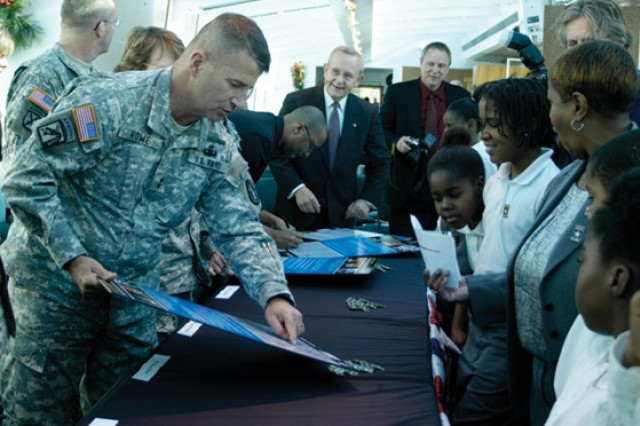 Maj. Gen Richard J. Rowe Jr., commanding general, Military District of Washington, shows kids from Amidon-Bowen elementary school signatures on the Army Community Covenant document.  Various District and Army leaders attended the signing on the Odyssey at the Southwest Waterfront in Washington, D.C.