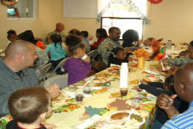 Soldiers, spouses and their children gather Nov. 19 at the  Fort McPherson Child Development Center to share a Thanksgiving meal with the center staff. Everyone received a plate stuffed with turkey and ham, green beans, rice, sweet potatoes, rolls and dessert.