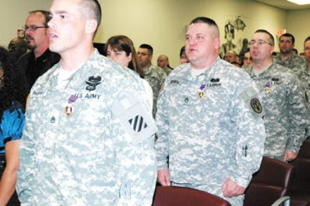 Purple Heart recipients Staff Sgt. Cypress Phipps, Staff Sgt. Michael Henning and Spc. David Talbot sing the 'Dog Face Soldier Song' during their Purple Heart ceremony, Nov. 20 at Winn Army Community Hospital. Phipps, Henning and Talbot were assigned to a 3rd ID unit at the time of their injuries and are now assigned to the Warrior Transition Battalion.