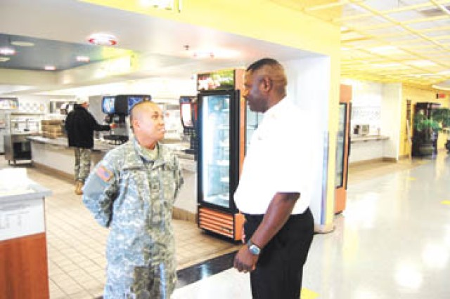 CAB DFAC Manager, Sgt. 1st Class Samuel Sprewer, 4/3 Avn., converses with Pfc. Donny Naovagangsy, 2/3 Avn., after lunch.