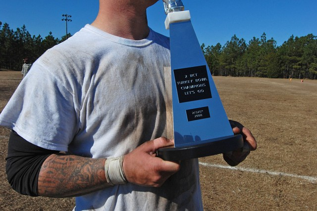 "A Paratrooper from the 2nd Battalion, 325th Airborne Infantry Regiment, 2nd BCT, 82nd Airborne Division gives a kiss to the coveted Turkey Bowl Cup, awarded every year to the team that wins the ""Turkey Bowl"" Thanksgiving flag football game at Fort Bragg, NC. This year's contest pitted the ""Golden Griffins"" of the 407th Support Battalion against the 2-325 AIR ""White Falcons."" The White Falcons won the game."