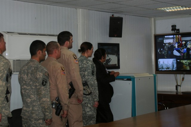 Soldiers at CJTF-101 Headquarters at Bagram look at the video teleconferencing screen as former Staff Sgt. Gary Harris is presented with the Bronze Star and Silver Star, at Fort Campbell, Ky.