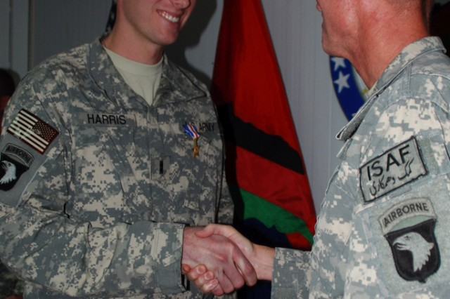 Chief Warrant Officer Jonathan Harris receives a handshake from Maj. Gen. Jeffrey Schloesser, commander, 101st Airborne Division, after being presented the Silver Star during an award ceremony at Combined Joint Task Force-101 Headquarters on Nov. 28.
