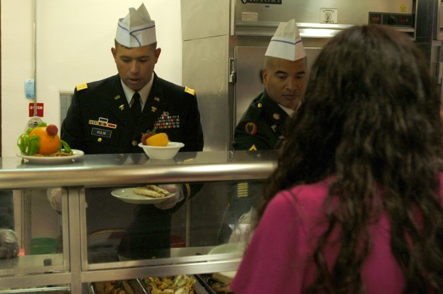 Maj. Brian Kulm, comptroller, 15th Sustainment Brigade, 13th Sustainment Command (Expeditionary),  serves some turkey to a Thanksgiving meal customer at the Freeman Café dining facility Nov. 27. Freeman took 1st Place in the annual Fort Hood Thanksgiving dining facility competition.