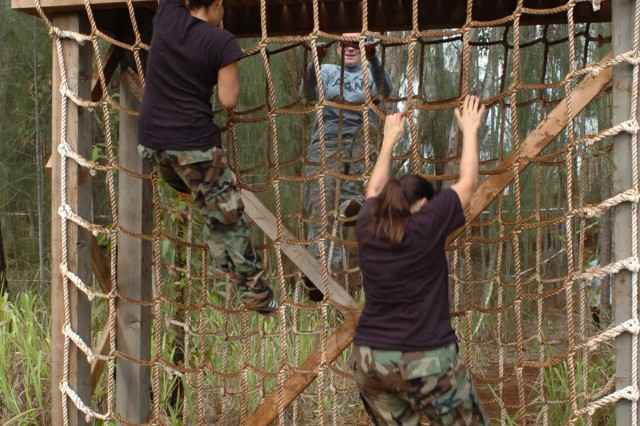 A team of 2nd Squadron, 6th Cavalry spouses scale a cargo netting obstacle during the unit's Spouse Spur Ride Nov. 15 at Schofield Barracks, Hawaii.