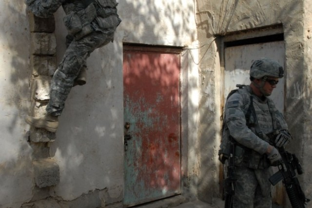 Staff Sgt. Brian Massey, with Company C, 3rd Battalion, 7th Infantry Regiment, 4th Brigade Combat Team, 3rd Infantry Division, climbs to the roof of a house near Musayyib during a patrol Oct. 5.