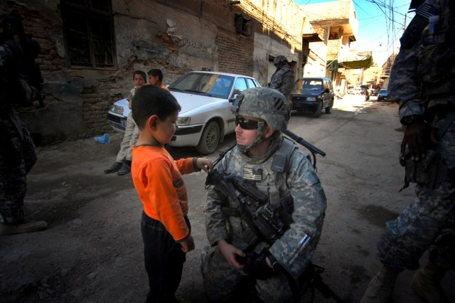 1st Lt. Zachary Boes, Company C, 3rd Battalion, 7th Infantry Regiment, 4th Brigade Combat Team, 3rd Infantry Division, speaks with a young resident of Musayyib during a patrol March 7.