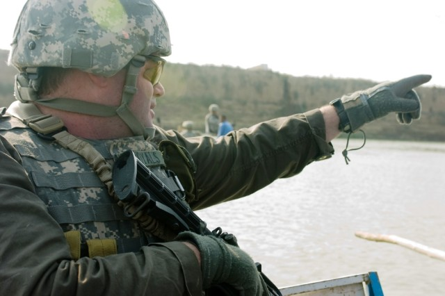 Jimmy Royals, a civilian police assistance trainer, points out an object of interest on the banks of the Tigris River during a combined patrol between the Iraqi Police and the U.S. Army military police in al Kut, Nov. 24
