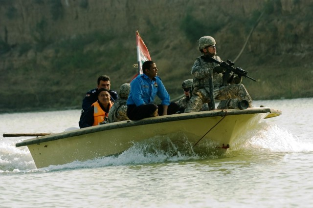 Sgt. 1st Class Joseph Marcy, 511th Military Police Company, keeps a sharp eye on the banks of the Tigris River from the bow of his boat as others in the crew watch the stern and sides during a combined Iraqi Police and U.S. Military Police patrol in al Kut, Iraq, Nov. 24, 2008.