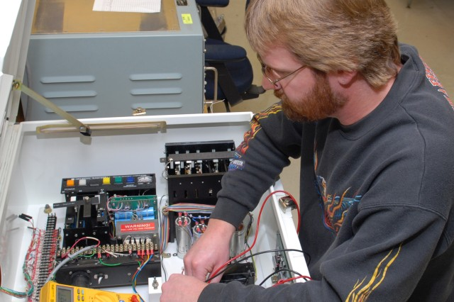 Gary Halterman, electronics mechanic, performs voltage verification on the sensor interface control of the Ambient Temperature and Dewpoint Measurement set.