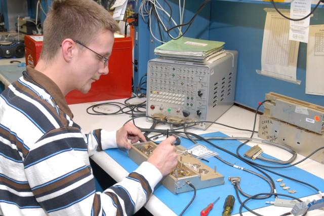 Matthew Carlson, student trainee electronics worker, adjusts variable capacitors in the 100 watt amplifier.