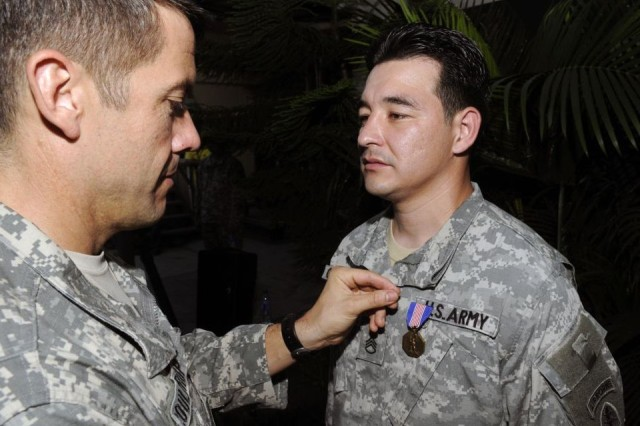 Col. Bill Coultrup, commander of Joint Special Operations Task Force-Philippines, pins the Soldier's Medal on Staff Sgt. Ruben D. Gonzalez as part of a ceremony Thanksgiving Day, Nov. 27.  Gonzalez was awarded the medal for risking his life to save three Filipino students from drowning.