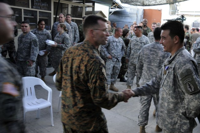 Fellow members of the Joint Special Operations Task Force-Philippines line up to congratulate Staff Sgt. Ruben D. Gonzalez after he was awarded the Soldiers Medal on Thanksgiving Day.