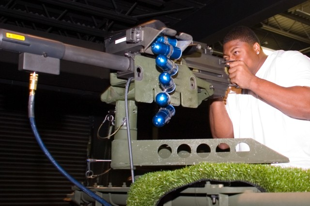 Dallas Cowboys player and defensive end Stephen Bowen tries his hand at the simulated MK-19 grenade machine gun at the Engagement Skills Trainer 2000 during his and Cowboys teammate Jay Ratliff's visit to Fort Bliss.