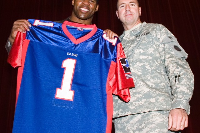 Col. John Rossi, Fort Bliss deputy commanding general and chief of staff, stands with visiting former NFL player Herschel Walker as he holds up his honorary Fort Bliss football jersey after a motivational speech Nov. 6 at Soldier Hall.