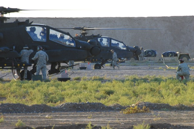 Soldiers from Company E, 4th Battalion, 4th Aviation Regiment, Combat Aviation Brigade, 4th Infantry Division, Multi-National Division - Baghdad, refuel an AH-64D Apache attack helicopter using an Advanced Aviation Forward Area Refueling System during a training exercise at Camp Taji, Nov. 19.