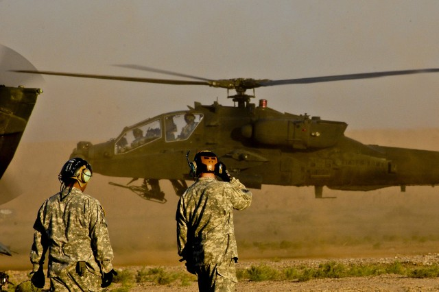 Two Soldiers from Company E, 4th Battalion, 4th Aviation Regiment, Combat Aviation Brigade, 4th Infantry Division, Multi-National Division - Baghdad, prepare to begin refueling operations as an AH-64D Apache attack helicopter lands at an Advanced Aviation Forward Area Refueling System site at Camp Taji, Nov. 24.