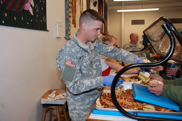 Staff Sgt. Colin Angele serves hot garlic bread to a hungry patron.