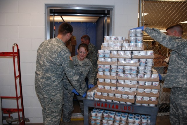 Left to right - Sgt. Burch Parshall, Capt. Christy Orser, and Staff Sgt. Colin Angele, from the S2 Division, 1st Space Brigade, SMDC/ARSTRAT, move a pallet of yogurt from the basement food storage locked in the Marian House Soup Kitchen, Colorado Springs, Colo., onto an elevator in preparation for the daily meal served.