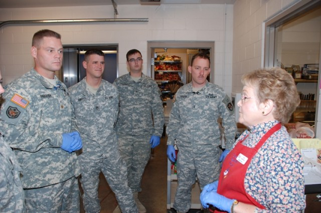 Soldiers from the S2 Division, 1st Space Brigade, SMDC/ARSTRAT, receive marching orders from Iris Lucas, supervisor, Marian House Soup Kitchen, Colorado Springs, Colo., prior to manning their stations in the assistance of serving the daily hot meal, on November 25.  Seen left to right are Maj. Stephen Parrish, Staff Sgt. (need first name) Angele, Sgt. Burch Parshall, and Chief Warrant Officer 2 Eric Schaub. This community service event is part of a teambuilding program within the S2.