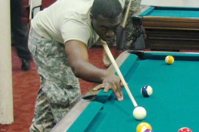 Pvt. Travis Williams lines up for a shot at the free pool tables during the sixth annual Salute to the Military on Nov. 23 at the Diane Campbell Recreation Center.