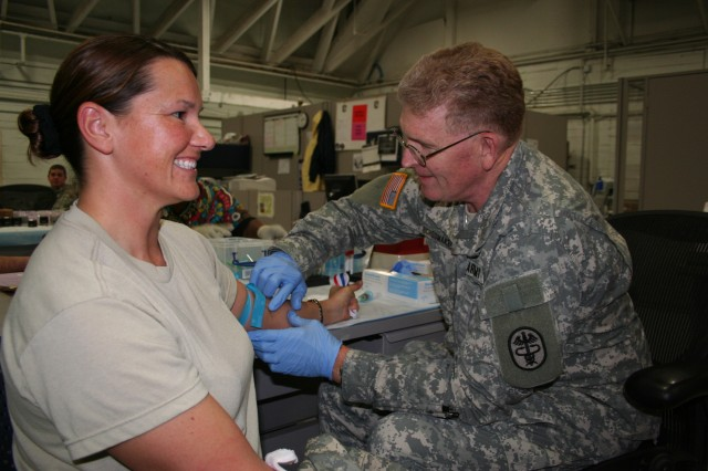 Lt. Gen. Eric B. Schoomaker prepares to draw blood from Cpt. Misty James, 129th Combat Sustainment Support Battalion Soldier, as she completes her reintegration from her 13-month tour from Iraq.  The 42nd Army Surgeon General toured Fort Campbell's reintegration site to see how Soldiers are handling redeployment.