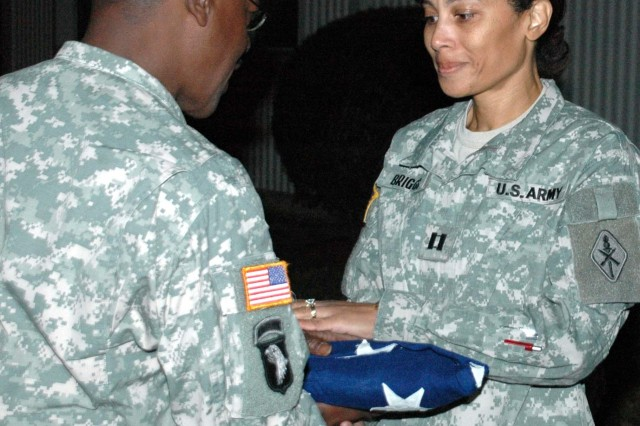 Command Sgt. Maj. Reginald Battle, command sergeant major for the 59th Ordnance Brigade, hands a tearful Capt. Bernita Briggs, also of 59th, her grandfather's cased flag. The flag, which belonged to the late William Dennis Lavergne Sr., Briggs' grandfather, flew Nov. 18, some 90 years after Lavergne was discharged from the military.