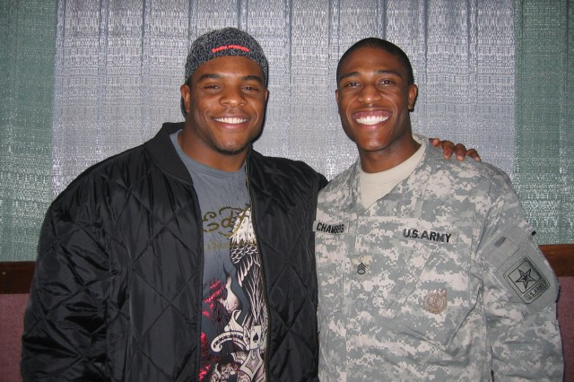 Staff Sgt. Marcelus Chambers, a recruiter with the Chicago Recruiting Battalion, takes advantage of a photograph opportunity with Jason McKie, starting fullback for the Chicago Bears, during a Military Family Movie Night event sponsored by the Jason McKie Foundation Dec. 1 in Gurnee, Ill.