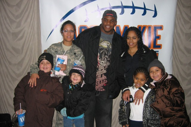 Jason McKie, starting fullback for the Chicago Bears, shares a moment with Spc. Terie King and her family at a Military Family Movie Night event sponsored by the Jason McKie Foundation Dec. 1 in Gurnee, Ill.