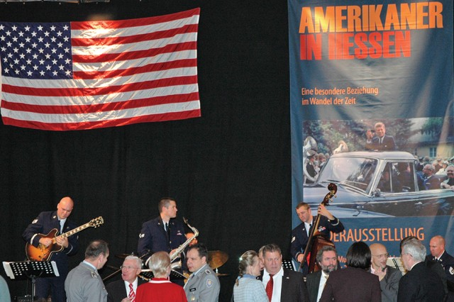"American and German dignitaries and citizens mingle during the opening of the ""Americans in Hessen"" exhibition in Hanau, Germany, as members of the U.S. Air Force Europe Jazz Combo perform on stage"