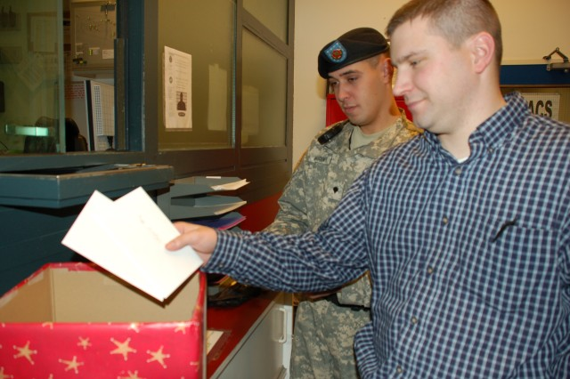 Investigator Craig Kosobucki and Specialist Claudio Fiornascente, of USAG Schinnen's Military Police, retrieve cards from a collection box for the Red Cross Holiday Mail Call program, which sends cards and letters to wounded warriors at Walter Reed Medical Center.