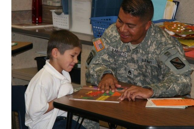 CUTLINE:  FORT CARSON, Colo.-Staff Sgt. Carlos Barreto gives first grader Ukiah Reyes some one-on-one guidance, while serving as a teacher's aide at Fountain-Fort Carson's Patriot Elementary.