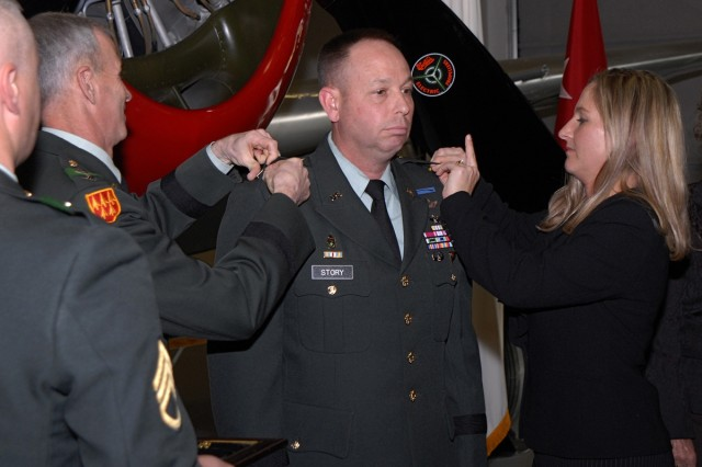 Col. Kurt Story is promoted to the rank of brigadier general by his wife Holly and Lt. Gen. Kevin T. Campbell, during a ceremony at the Peterson Air and Space Museum Dec. 2.