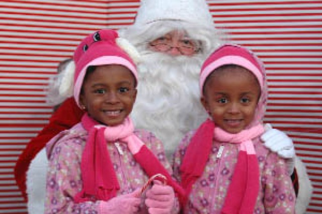Skyelar and Solenne Montgomery, 5, pose for pictures with Santa. The girls attended the Christmas Tree Lighting Ceremony held Dec. 2 at Fort McPherson with their mother, Maj. Bronte Montgomery, a military law attorney with U.S. Army Forces Command (FORSCOM)'s Office of the Staff Judge Advocate.