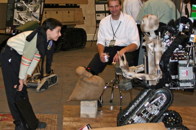 An eCybermission student says hello to BEAR, the Battlefield Extraction Assistance Robot.
