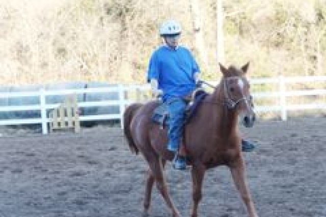"""Spc. Kevin Snow, an Iraq war veteran of the Warrior Transition Battalion, rides """"Red"""" through a variety of gaits and obstacles to improve his balance and confidence."""