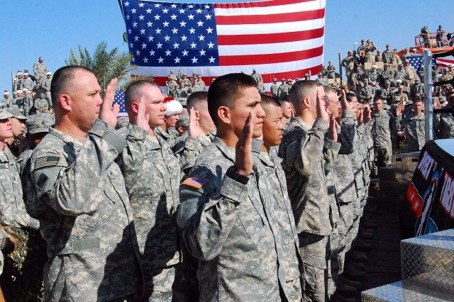 CAMP VICTORY, Iraq - Multi-National Division - Baghdad Soldiers  gather around the World Wrestling Entertainment ring, raise their right hand and re-enlist to serve their country before the WWE wrestlers took the ring during the Tribute to the Troops Tour held in front of the Al Faw Palace on Dec. 5.