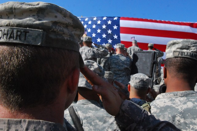 CAMP VICTORY, Iraq -Soldiers from all around the Victory Base Complex salute the American flag during the playing of the National Anthem before the World Wrestling Entertainment wrestlers took the ring during the Tribute to the Troops Tour, held in front of the Al Faw Palace on Dec. 5.
