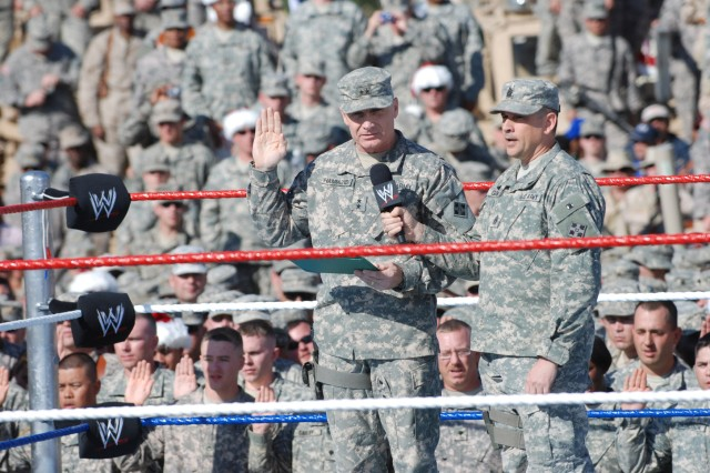 BAGHDAD, Iraq - Maj. Gen. Jeffery Hammond (left), a native of Hattiesburg, Miss., the commanding general of Multi-National Division - Baghdad and the 4th Infantry Division, accompanied by Command Sgt. Maj. John Gioia, the division's senior enlisted leader, administers the oath of enlistment to 100 Multi-National Division - Baghdad Soldiers reenlisting during the World Wrestling Entertainment Inc.'s Tribute to the Troops Tour in front of the Al Faw Palace on Camp Victory Dec. 5. The event marks the sixth year in a row that WWE superstars have come to entertain U.S. troops stationed on the front lines in Iraq.