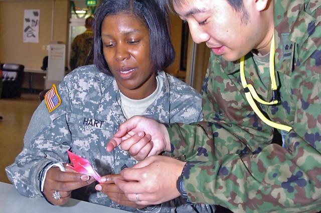 Sergeant 1st Class Rhonda Hart works with JGSDF 1st Lt. Toshyasu Karinuma to create a Japanese Origami crane.