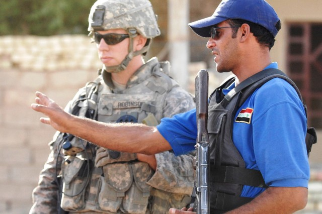 """An Iraqi police officer shows Cpl. Randall Robinson, from Charleston, S.C., the different features of a checkpoint while on a patrol in the town of Narhwan, Oct. 9, 2008. The """"Headstart"""" language program developed by the Defense Language Institute hopes to give Soldiers more knowledge of the languages they may encounter on a deployment."""