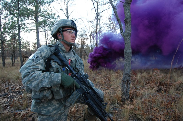 A Paratrooper from 2nd Battalion, 325th Airborne Infantry Regiment, 2nd Brigade Combat Team, 82nd Airborne Division, gets ready to assault an objective under cover of smoke during a live fire exercise at Fort Bragg Dec. 5.